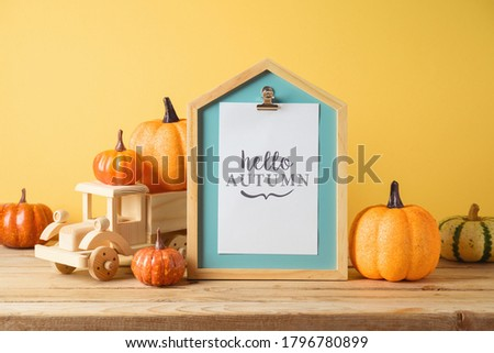Hello Autumn concept with picture frame, toy truck and pumpkin decor on wooden table over yellow background. Fall season greeting card.