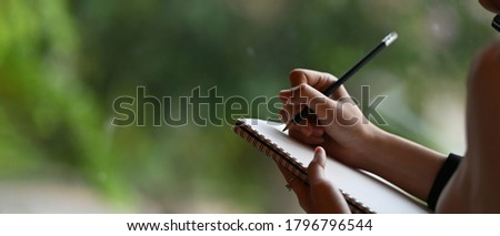 Cropped image of a businesswoman's hand is taking notes while standing over the office glass wall. Royalty-Free Stock Photo #1796796544