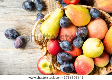 Assortment of fruits in a basket on the table. There are a lot of different raw fruits in the basket. Plums, peaches, apples and pears on the table. Healthy diet. Top view with space for text Royalty-Free Stock Photo #1796808649