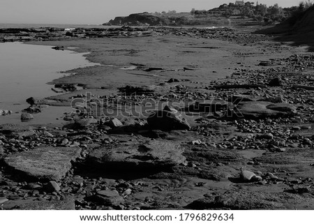 monochrome pictures of Agia Marina, Cyprus shoreline littered with sandstone and lava rock at low tide.