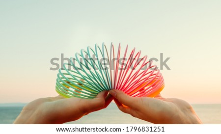 Female hands with rainbow toy spring against sea landscape. Lgbt month,  homosexual rights, gay pride parade.