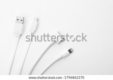 Charge cables on white background, top view. Modern technology Royalty-Free Stock Photo #1796862370