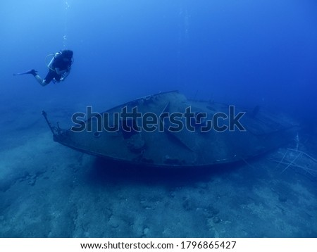 scuba divers exploring and discovering the ship wreck underwater deep sea bottom Royalty-Free Stock Photo #1796865427