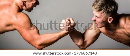 Arm wrestling. Two men arm wrestling. Rivalry, closeup of male arm wrestling.