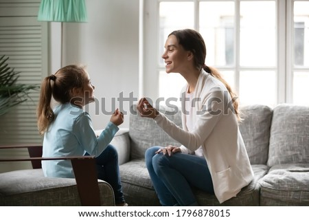Side view adorable small preschool girl involved in speaking lesson with professional mixed race physiotherapist. Happy young mother teaching little daughter correct sounds pronunciation at home. Royalty-Free Stock Photo #1796878015
