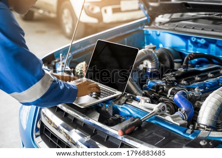 Mechanic Asian man close up using laptop computer examining tuning fixing repairing car engine automobile vehicle parts using tools equipment in workshop garage support service in overall work uniform Royalty-Free Stock Photo #1796883685