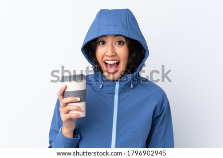 Mixed race woman wearing winter clothes with the hood on and holding a hot takeaway coffee over isolated white background with surprise and shocked facial expression #1796902945