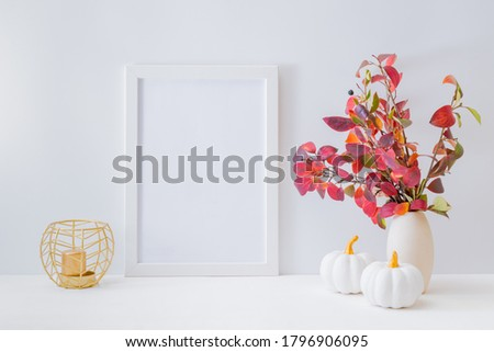 Home interior with decor elements. Mockup with a white frame, colorful autumn leaves in a vase on a light background