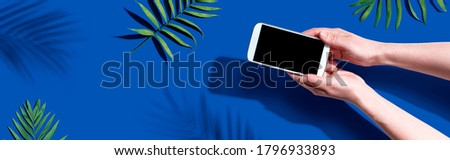 Smartphone with tropical palm leaves and shadow - flat lay Royalty-Free Stock Photo #1796933893