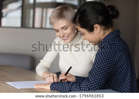 Smiling young professional insurer showing place for signature on paper contract to satisfied female indian client. Happy diverse businesswomen establishing cooperation by signing agreement in office. Royalty-Free Stock Photo #1796961853