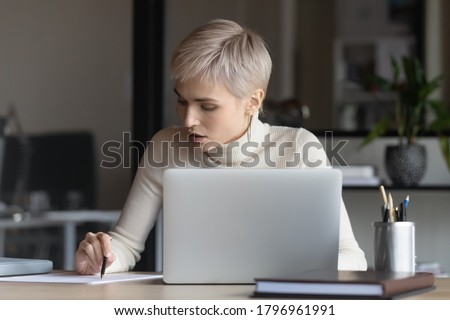 Front view focused young businesswoman sitting at table with computer, reading contract terms of conditions, checking paper report, analyzing marketing research results or editing document in office.