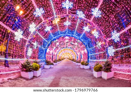 Moscow. Russia. Tunnel of Christmas garlands. A long tunnel of glowing garlands. New Year's illumination on the streets of Moscow. Snow. Walks in the winter capital. Tour of Russian cities. Royalty-Free Stock Photo #1796979766
