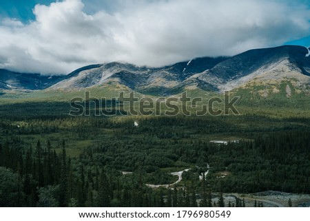 Foggy mountain peaks on the background of the tundra plants and forest. Mountain landscape in Kola Peninsula, Arctic