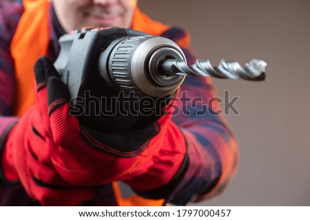 Driller. Man brings a electric drill to the camera. Worker wants to drill a camera. Concept - man is drilling a screen. Borer drills are very close to the screen. Concept - purchase of a drill. #1797000457