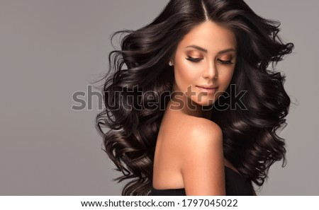 Beauty brunette girl with long  and   shiny wavy black hair .  Beautiful   woman model with curly hairstyle . Royalty-Free Stock Photo #1797045022