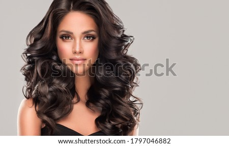 Beauty brunette girl with long  and   shiny wavy black hair .  Beautiful   woman model with curly hairstyle . Royalty-Free Stock Photo #1797046882