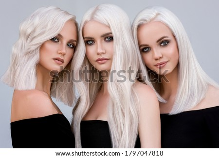 Three beautiful girls with hair coloring in ultra blond. Stylish hairstyle curls done in a beauty salon. Fashion, cosmetics and makeup