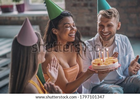 Happy birthday. A woman blowing out candles during the birthday party