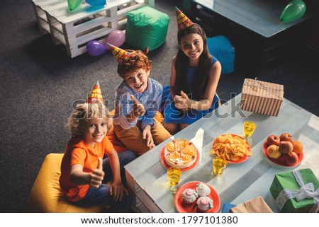 Bday. Three kids sitting at the table and celebrating bday
