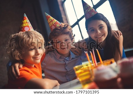 Happy kids. Three kids celebrating bday and smiling nicely