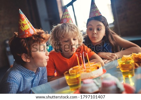 Bday cake. Three kids celebrating bday and blowing out candles