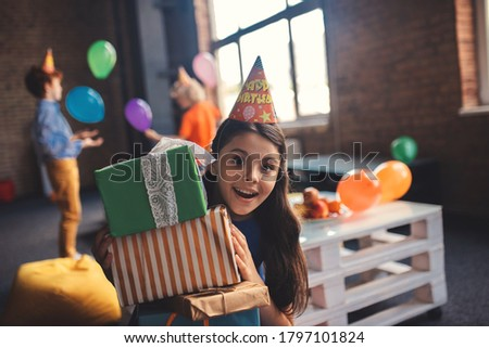Feeling happy. Cute girl in a hat holding presents and feeling happy