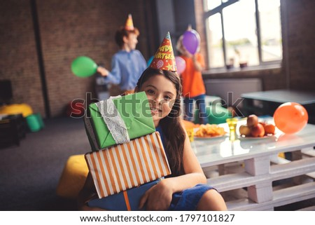 Happy girl. Cute girl in a hat holding presents and looking happy