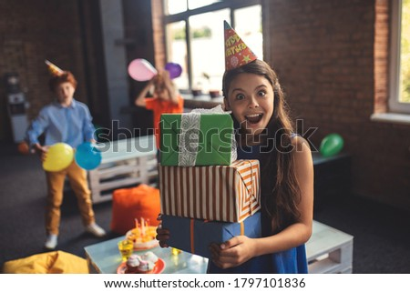 Bday. Pretty girl in a hat holding presents and looking excited