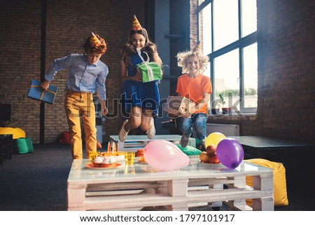 Happy kids. Three friends in bday hats jumping and looking happy