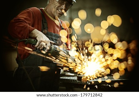 Industrial worker cutting and welding metal with many sharp sparks Royalty-Free Stock Photo #179712842
