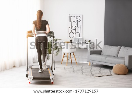 Sporty young woman training on treadmill at home #1797129157