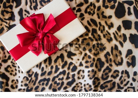 leopard fabric background with white gift box and red ribbon