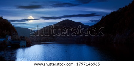 panorama of tarnita lake in romania at night. beautiful nature scenery in autumn in full moon light. gorgeous sky with glowing clouds Royalty-Free Stock Photo #1797146965