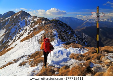 Mountaineer near the summit post after climbing a snow covered ridge #179715611