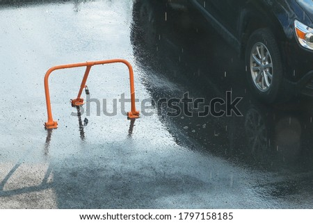 red parking lot barrier with padlock for private parking with a fence background in rain #1797158185