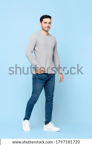 Full length portrait of young handsome Caucasian man standing with hand in pocket while looking at camera in isolated studio blue background Royalty-Free Stock Photo #1797181720