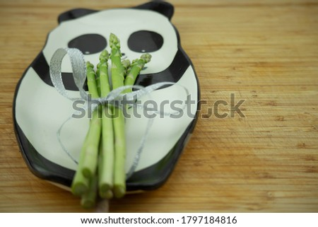 A bunch of fresh asparagus lies on a plate with a picture of a panda bear. On a wooden cutting board.