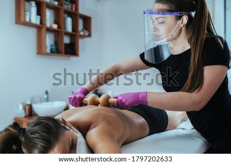 Working Safely During Coronavirus Crisis. Masseuse massaging client with gloves and face visor at Beauty Spa Wellness Center during COVID-19 pandemic Royalty-Free Stock Photo #1797202633