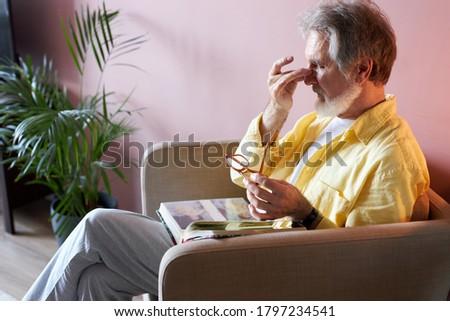 senior caucasian sad man with photo album missing his wife, depressed widower at home