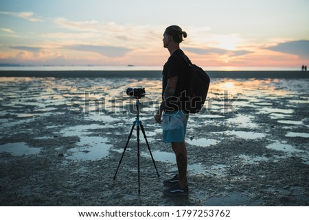 Silhouette of man taking photos with his camera at sunset beach #1797253762