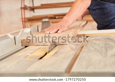 Artisan saws wood board with the circular saw in carpentry or joinery #1797270250