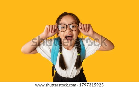 Back To School. Funny Korean Schoolgirl In Glasses Posing Having Fun Smiling To Camera On Yellow Background. Studio Shot