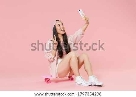 Full length portrait of cheerful young asian woman in cap isolated on pastel pink background. People lifestyle concept. Sit on skateboard, doing selfie shot on mobile phone, showing victory sign