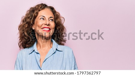 Middle age beautiful woman wearing casual denim shirt standing over pink background smiling looking to the side and staring away thinking. Royalty-Free Stock Photo #1797362797