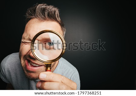 man see through magnifying glass on the black backgrounds. Big man eye Royalty-Free Stock Photo #1797368251