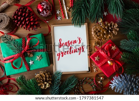 Season's greetings text on cards with gift box present and ornament element on wood table background.winter season activity ideas Royalty-Free Stock Photo #1797381547