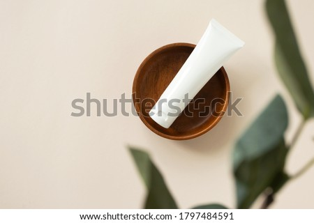 Cream moisturizer on wooden plate on light beige background with blur eucalyptus leaf, above. Natural organic eco cosmetic beauty product. White plastic tube mockup for lotion, cleanser or shampoo  Royalty-Free Stock Photo #1797484591