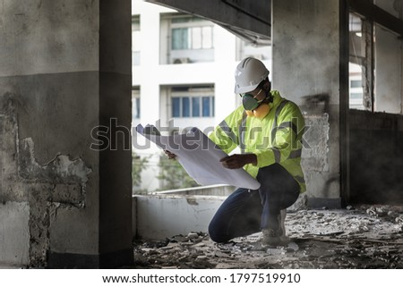 Civil Engineer People wearing face mask and safety helmet while looking to detail in drawing on construction site. Surveyor and checking in the Construction building for Demolishing and Renovate #1797519910