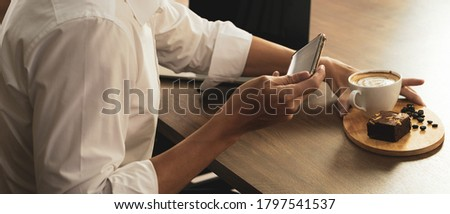 banner picture of businessman using smartphone to take a photo of coffee and brownie before eating breakfast in the cafe