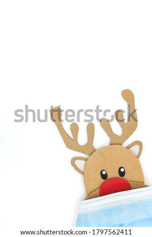 Cardboard cutout of cute reindeer peeking while wearing a face mask. Covid during Christmas season concept.